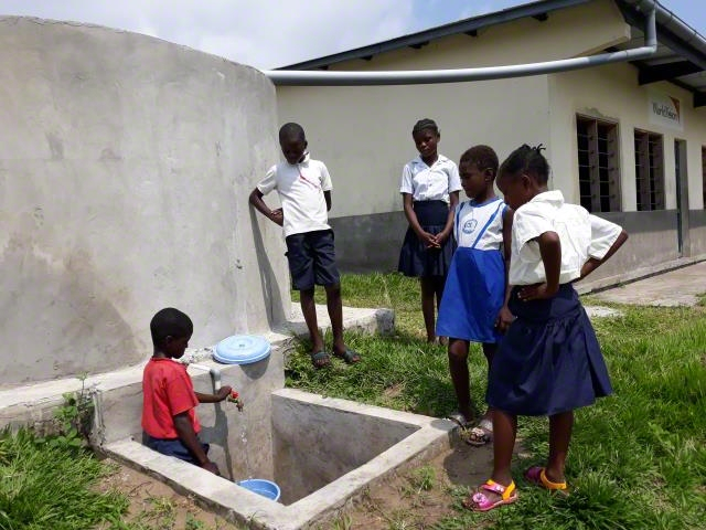 students draw water from a cistern built